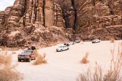 Jeeps et touristes bédouins de voiture du ` s dans lui en désert de Wadi Rum en Jordanie Photographie stock