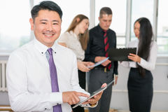 Jefe asiático ejecutivo que usa la PC de la tableta con su equipo del negocio Fotos de archivo libres de regalías
