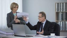 Jefe cansado enojado en el ayudante, los éticas corporativos, comportamiento inadecuado del trabajo metrajes