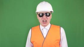 Jefe caucásico enojado en vidrios negros y un casco protector y en un chaleco de la señal que grita en su subordinado y almacen de metraje de vídeo