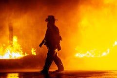 Jefe de bomberos que camina delante del fuego durante un ejercicio contraincendios Imágenes de archivo libres de regalías