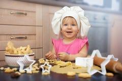 Jefe del pequeño niño que cocina las galletas en la cocina Fotografía de archivo