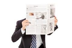 Jefe disimulado que mira a escondidas a través de un agujero en periódico Foto de archivo