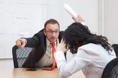 Jefe enojado que enciende al colega femenino mostrando la puerta con su índice Fotografía de archivo libre de regalías