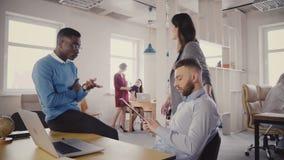 Jefe femenino caucásico que ayuda a colegas multiétnicos jovenes El encargado de la mujer motiva a empleados en la oficina modern metrajes