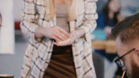 Jefe femenino europeo hermoso joven que pone las notas de papel en la tabla de la oficina mientras que equipo principal en la reu almacen de metraje de vídeo