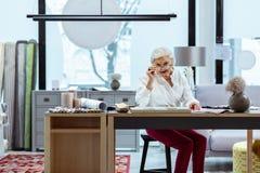 Jefe femenino mayor en vista de los papeles y cálculos el hacer en oficina imagenes de archivo