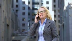 Jefe femenino mayor que siente el hablar enojado y decepcionado en el teléfono, fracaso almacen de video