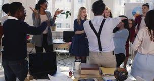 Jefe femenino moreno feliz joven de la diversión que celebra los logros que bailan con los colegas multiétnicos en la oficina mod almacen de video