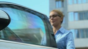 Jefe femenino que recibe llaves al vehículo de lujo de distribuidor autorizado, de préstamo de coche o de compra almacen de metraje de vídeo