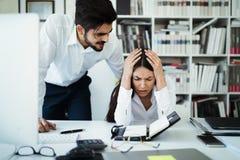 Jefe irritado enojado que reprende al empleado asustado ser encendido, acusando de error en informe, mún trabajo foto de archivo libre de regalías
