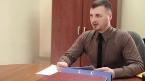 Jefe joven en su oficina que habla con un empleado almacen de metraje de vídeo