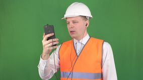 Jefe masculino caucásico joven que habla en la llamada video del teléfono en auriculares en el emplazamiento de la obra con el cl almacen de metraje de vídeo