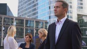 Jefe masculino que mira el fondo cercano de los miembros de equipo del negocio del reloj que habla almacen de metraje de vídeo