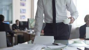 Jefe masculino que mira a través de la documentación y del té de consumición, colocándose en su oficina metrajes