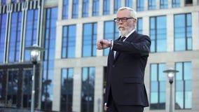 Jefe mayor que espera a la secretaria joven que mira el reloj, socio comercial impuntual imagen de archivo libre de regalías