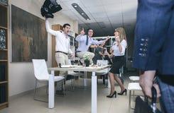 Jefe que llega a la oficina mientras que trabajadores que bailan adentro foto de archivo