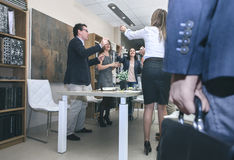 Jefe que llega a la oficina mientras que trabajadores que celebran fotografía de archivo libre de regalías