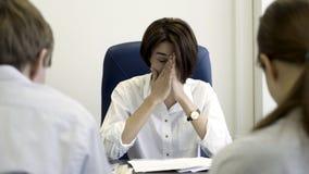 Jefe serio de la mujer que regaña a los empleados para el mún resultado de negocio Jefe furioso que regaña a internos frustrados  fotos de archivo