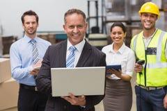Jefe sonriente que usa el ordenador portátil delante de sus empleados imágenes de archivo libres de regalías