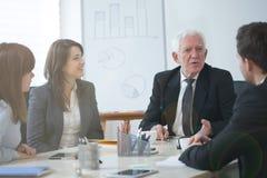 Jefe y empleados mayores durante conferencia Imágenes de archivo libres de regalías