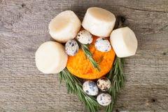 Jefes del diversos queso, huevos de codornices y romero en un t de madera Foto de archivo libre de regalías