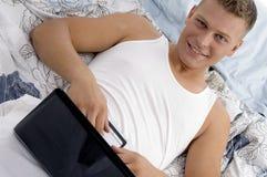 jego laptopu męski kładzenia żołądek Obrazy Royalty Free