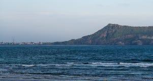 JEJU Ö, KOREA: Sikt av Seongsan Ilchulbong den vulkaniska kotten från staden på foothillen fotografering för bildbyråer