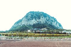 JEJU ISLAND, SOUTH KOREA - AUGUST 18, 2015: Small town located by the sea shore with big turtle shaped mountain behind it - Jeju I. JEJU ISLAND, SOUTH KOREA Stock Photo
