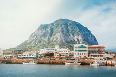 JEJU ISLAND, SOUTH KOREA - AUGUST 18, 2015: Small town located by the sea shore with a turtle shaped mountain behind it - Jeju Isl. JEJU ISLAND, SOUTH KOREA stock photos