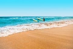 Jeju Island, South Korea - August 18, 2015: Two enthusiastic surfers swimming in the sea - Jeju Island, South Korea. Jeju Island, South Korea - August 18, 2015 Stock Image