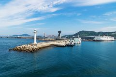 Jeju-si ferry terminal seen from the sea, Jeju-si, Jeju Island, South Korea. Jeju-si ferry terminal seen from the sea with lighthouse, Jeju-si, Jeju Island royalty free stock images