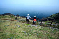Jeju Volcanic Island. Yong couple stand by blue ocean, with spring wild flowers surrounding,Jeju Volcanic Island,Korea Stock Image