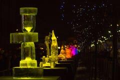 Jelgava/Letónia - 10 de fevereiro de 2017: Escultura de gelo amarela do relógio do tempo iluminado, com outras esculturas no fund fotografia de stock