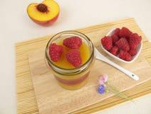 Jelled smoothie as layered dessert peach melba Stock Photo