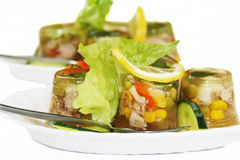 Jellied pork meat. And vegetables garnished with lettuce, cucumber and lemon Royalty Free Stock Photos