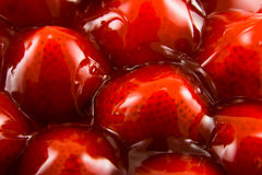 Jellied Strawberries. Several delicious looking strawberries in red jelly on a white background Stock Photo