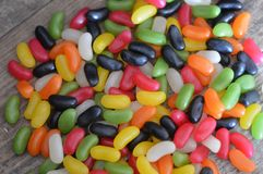 Jelly beans on a wooden backgroud. Jelly bean candy waiting to be eaten on a wooden backgroud stock images
