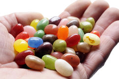 Jelly beans. Fruit jelly beans on hand, on white background royalty free stock photography