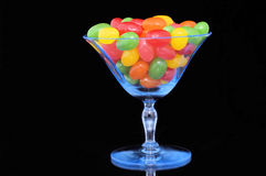 Jelly Beans anyone?. A  transparent blue desert glass is filled with colorful jelly bean candies. The background is black Royalty Free Stock Photos