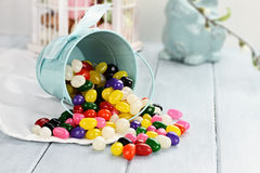 Jelly Beans. A blue tin bucket tipped over, spilling jelly beans onto a table. Shallow depth of field Stock Image