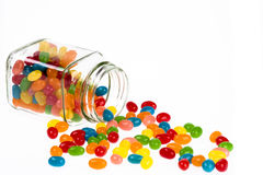 Jelly Beans candy spilled from glass jar isolated on white backg. Close up of a delicious Jelly Beans candy spilled from a glass jar isolated on a white Royalty Free Stock Photography