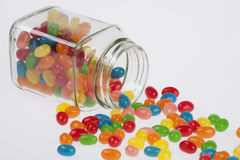 Jelly Beans candy spilled from glass jar on white backg. Close up of a delicious Jelly Beans candy spilled from a glass jar on a white background stock image