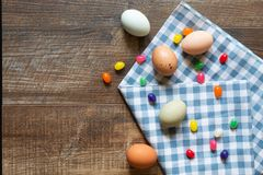 Jelly beans and colored eggs with blue and white gingham towel on wood background royalty free stock photography