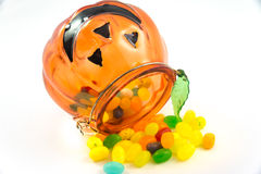Jelly beans drop from pumpkin glass isolated Stock Photography