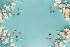 Jelly Beans and Floral Background. Jelly beans and spring flowers over a teal / blue background with room for copy space. Image shot from top view stock image