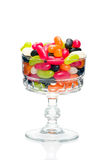 Jelly beans in a glass. Jelly bean sugar candy snack in stylish crystal glass bowl isolated on white Stock Photography
