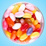 Jelly beans in glass on blue background Royalty Free Stock Photography