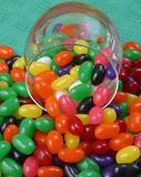 Jelly beans and glass jar. Macro view of colorful jelly beans spilling out of glass jar stock photos