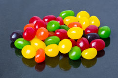 Jelly beans on glossy black Royalty Free Stock Images